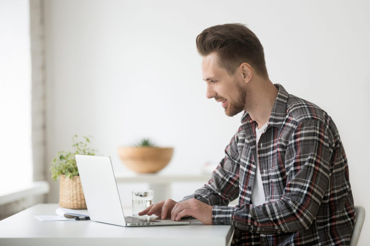 Smiling man freelancer working on laptop sitting at home office desk, happy casual young businessman looking at computer screen communicating online or using software for business or education